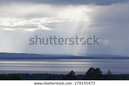 Showers and sun rays over a lake and it´s background. Landscape in evening lit.