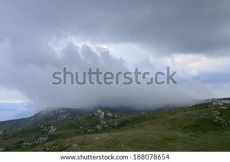 Showers in low mountains: a shred of a gray cloud sails over the steppe. Rainy day in the highlands of Crimea