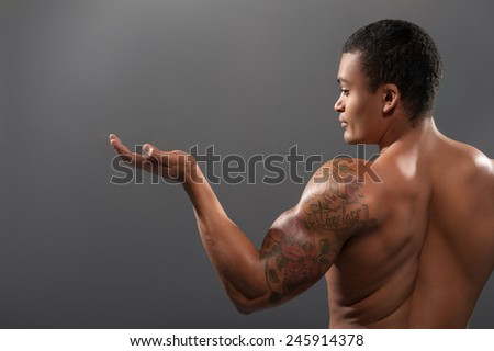 Showing copy space. Rear view of young shirtless African man with muscular body showing copy space while standing against grey background   - stock photo