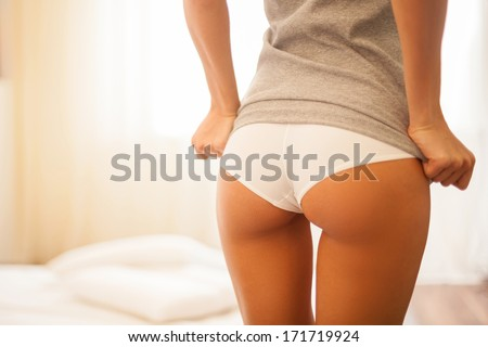 Showing her beautiful buttocks. Cropped image of beautiful young woman with perfect buttocks undressing while standing back to camera - stock photo