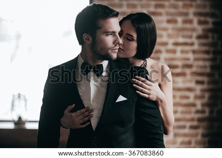Showing her love. Close-up beautiful young woman standing behind her boyfriend wearing suit and giving him a kiss in cheek - stock photo