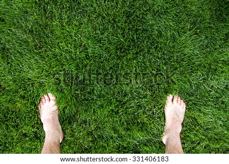 Showing only his feet a man is standing over some grass