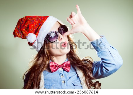 showing Pinocchio nose sign funny hipster girl in sunglasses wearing xmas santa hat over olive copy space background - stock photo