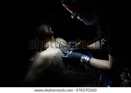Showing process of making a tattoo by professional girl artist in studio. Tattooist design in pattern dream catcher. Art on human body skin. Machine gun. Sexy woman concept. White and black ink.