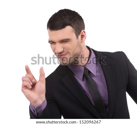 Showing the size. Confident young man in formalwear showing the size of something by fingers while isolated on white
