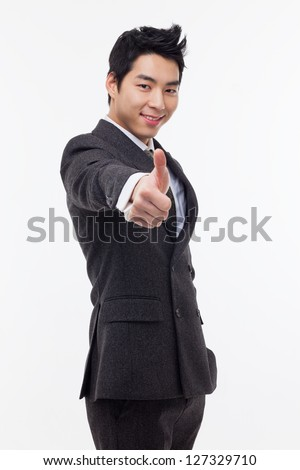 Showing thumb young Asian business man isolated on white background. - stock photo