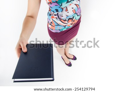 Showing woman holding book diary with copy space for your text or design. High angle view on white background. - stock photo