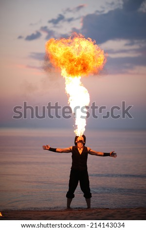Showman breathes fire standing in the water - stock photo