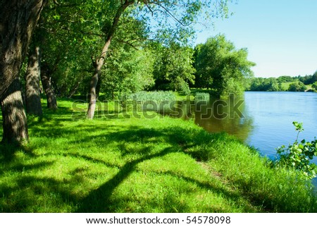 Shows the river, trees, grass and sky. - stock photo