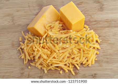 Shredded cheddar cheese on a brown background - stock photo