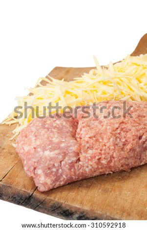 Shredded cheese and minced meat on a kitchen wooden board. - stock photo