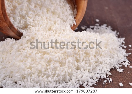 Shredded coconut in a wooden bowl on a wooden background