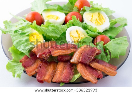 Shredded lettuce, cherry tomatoes, bacon and boiled eggs on a plate close-up with shallow depth of field