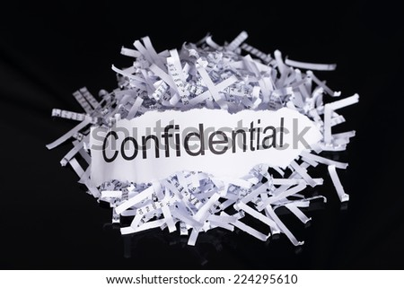 Shredded paper in data confidentiality concept over black background - stock photo