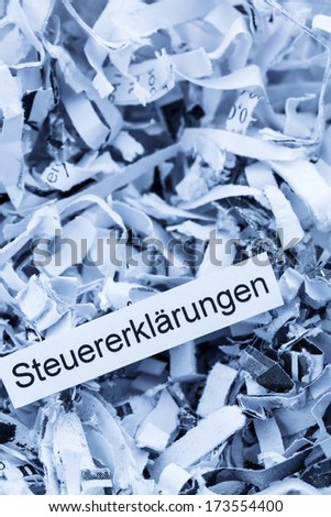 shredded paper tagged with tax returns, symbol photo for tax burden and retention requirements - stock photo