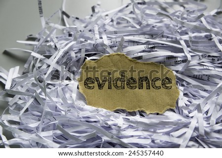 "Shredded paper with piece of brown paper in the center written ""Evidence"" - stock photo"