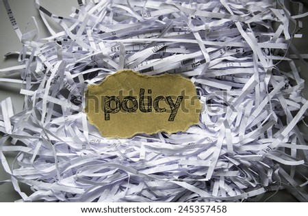 "Shredded paper with piece of brown paper in the center written ""Policy"" - stock photo"