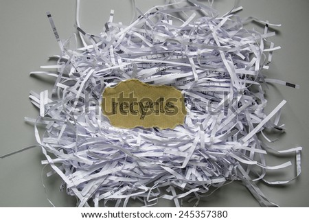 "Shredded paper with piece of brown paper in the center written ""Recycle"" - stock photo"