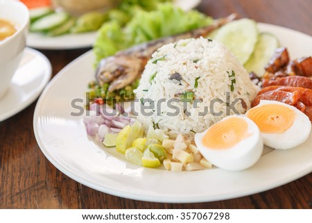 Shrimp and chili paste with fried mackerel, egg, Chinese sausage and vegetable in white plate on wood table. Thai food.