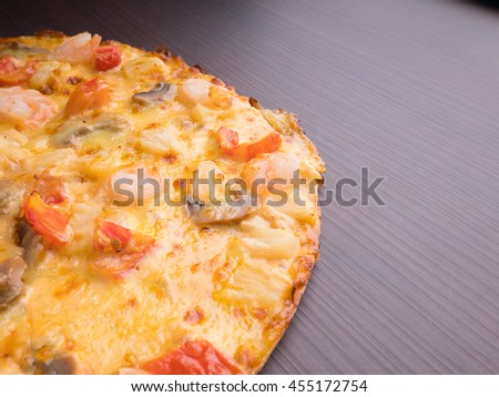 shrimp cocktail pizza with tomato and pineapple on brown wood table