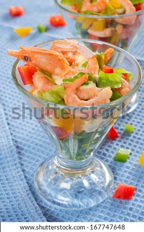 Shrimp cocktail with peppers, lettuce and sauce.