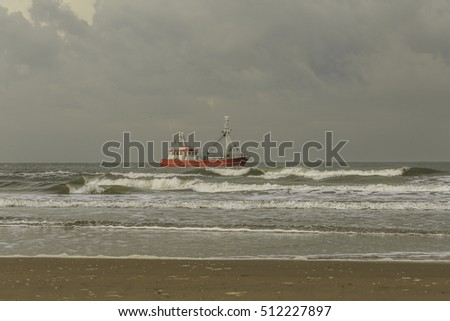 Shrimp fisherman with boat with trawl in the surf of the North Sea along the Dutch coast in very low water