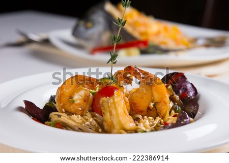 Shrimp on Top of Bed of Noodles in Bowl in Restaurant on Table - stock photo
