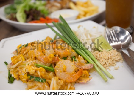 Shrimp pad Thai with other food on background - stock photo