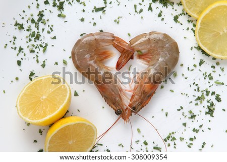 shrimp raw -  uncooked  fresh seafood scampi  natural organic on rustic wooden background-  sea food - shrimp placed in the heart as a symbol of love - stock photo