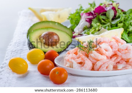 Shrimp salad ingredients - cooked, peeled shrimps, salad, tomato and avocado - stock photo