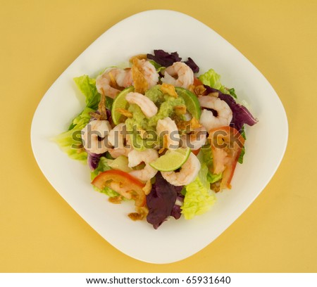 Shrimp salad seen from above with avocado paste, fried onions, tomato and purple cabbage.