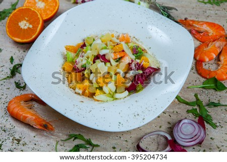Shrimp salad with citrus fruits. fruit and vegetable salad dish. Cooked shrimps with lemon and salad - stock photo