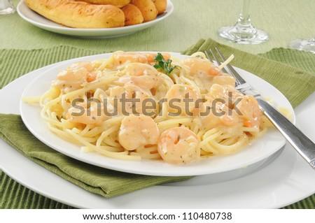 Shrimp scampi on spaghetti noodles with breadsticks - stock photo