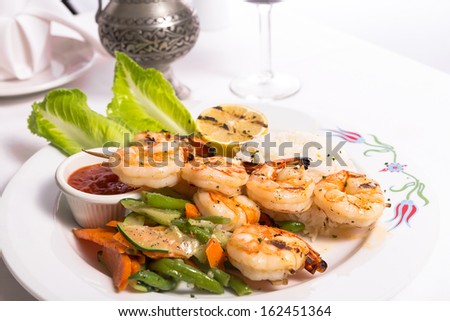Shrimp skewers are grilled and garnished with veggies and rice served on a white plate along with a silver pitcher - stock photo