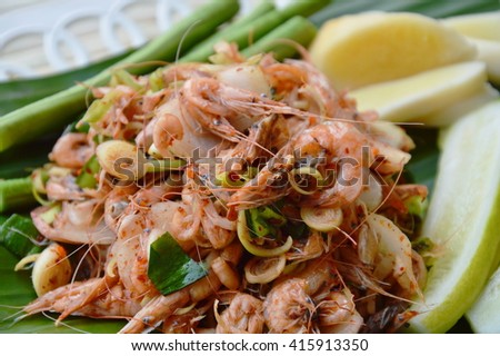 shrimp spicy salad with herb on fresh banana leaf - stock photo