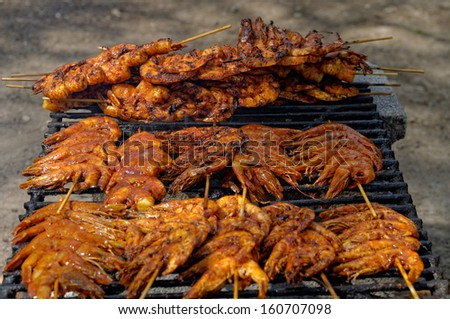 Shrimp spit with mexican chili sauce on grill, beach barbecue