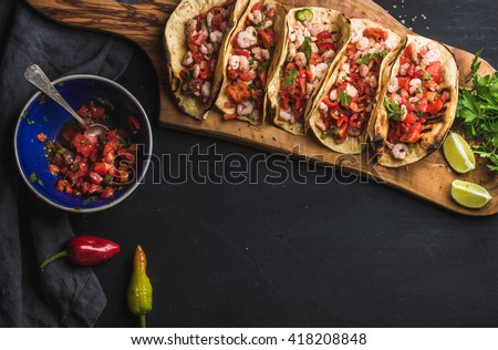 Shrimp tacos with homemade salsa, limes and parsley on wooden board over dark background. Top view, copy space. Mexican cuisine - stock photo