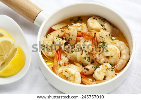 Shrimp with garlic butter, lemon and chives, in white serving pan. - stock photo