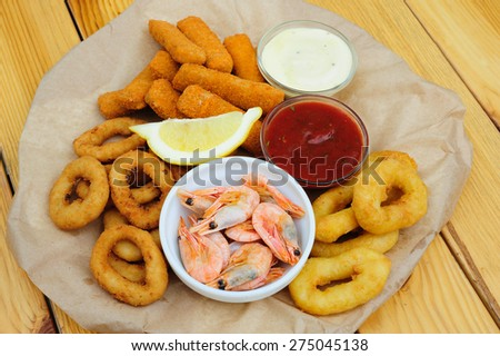 Shrimps, calmar rings and fish sticks with lemon and dip sauces, served as beer snacks - stock photo