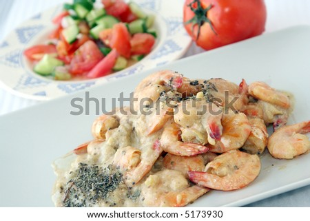 Shrimps dish with sauce and salad