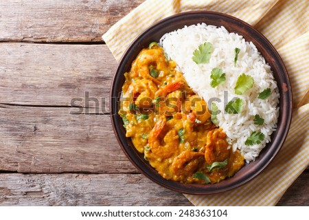 Shrimps in curry sauce and rice on a plate. horizontal view from above  - stock photo
