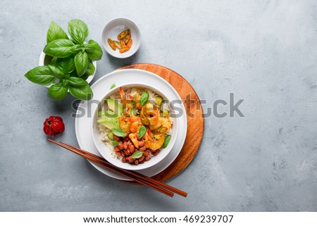 Shrimps in curry sauce and rice on a plate, selecive focus