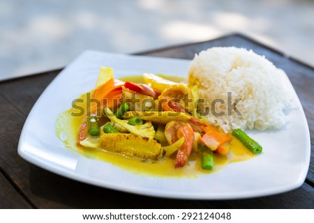 Shrimps in curry sauce with rice traditional Thai style on wooden table - stock photo