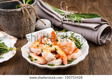 Shrimps in lemon sauce in a scallop shell dish, tinted image - stock photo