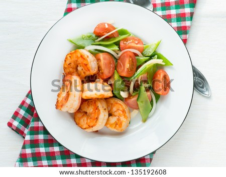 Shrimps (prawns) and fresh snow peas and tomato salad, overhead - stock photo