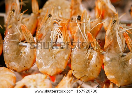 shrimps prawns  on grill skewers bbq, shallow dof - stock photo