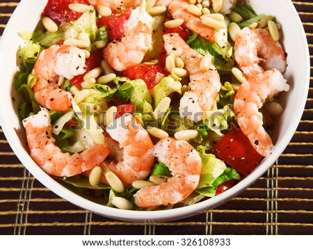 Shrimps salad with iceberg, pine nuts and tomatos