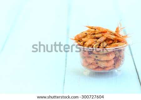 Shrimps. Sea products. One serving of cooked shrimp. Prepared shrimp on wooden blue background. - stock photo