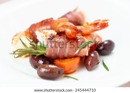 Shrimps with bacon, olives and rosemary, close-up - stock photo
