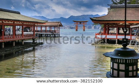 Shrines at the waterside in an island near Hiroshima. Tori gate in the background and a lamp in the foreground.